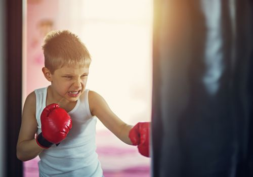 Little boy wearing boxing gloves hitting punching bag
