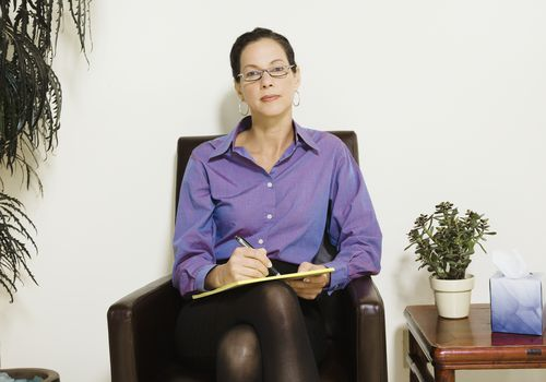 female psychiatrist holding notepad, sitting in chair