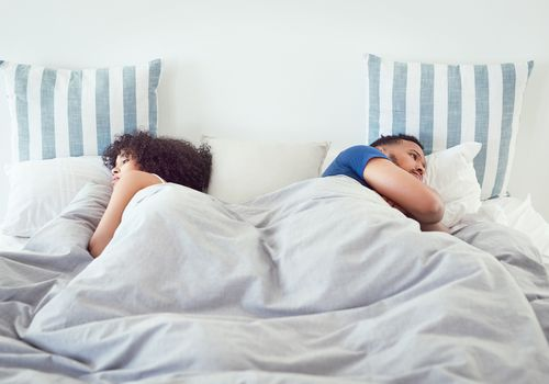 Couple sleeping with their backs turned on each other