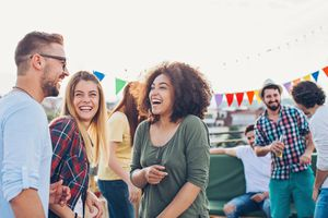 Group of young people chatting and laughing on a rooftop party.