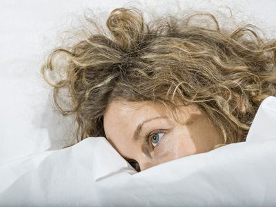 Woman in bed under white blanket