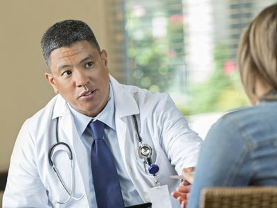 Mature Asian doctor prescribing medication to female patient