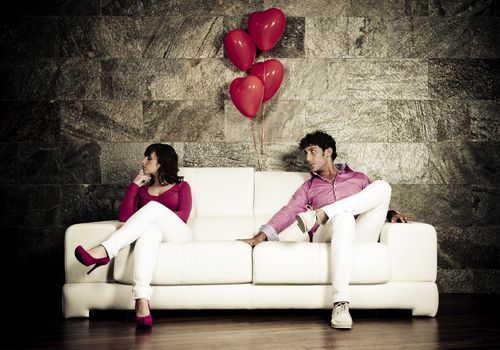 Upset couple sitting on opposite ends of a sofa