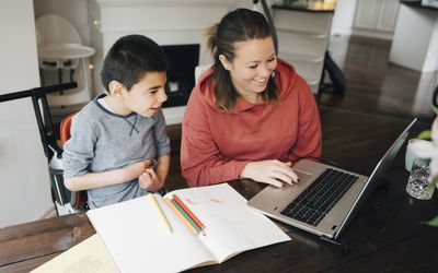 A young boy looking at a laptop with his mother