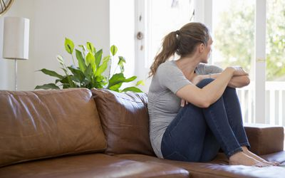 Woman sitting on sofa looking out of window