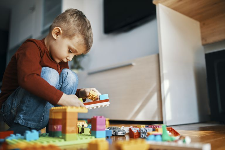 Toddler boy playing on the floor with blocks