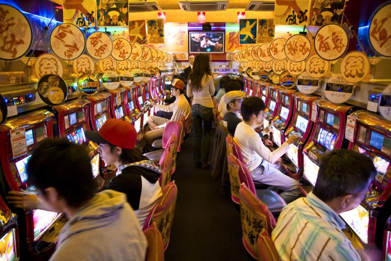 row of people playing slot machines