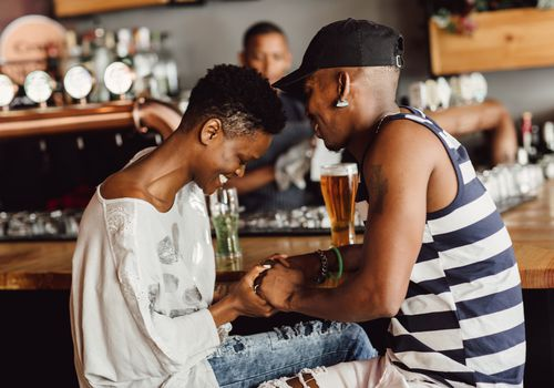 An african american couple having a drink together, laughing