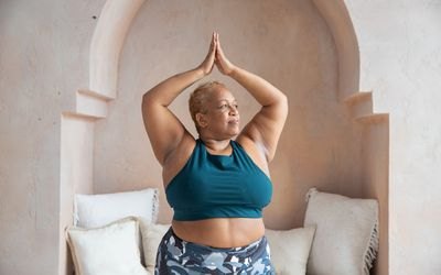 An older black woman is in workout gear doing yoga in a studio. She is curvy and loves her body. Stretching and mediating help her feel relaxed and strong.