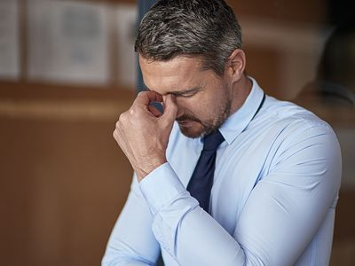 stressed businessman with his head down and fingers pinching his nasal bridge