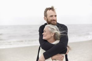 Adult son hugging senior mother on the beach
