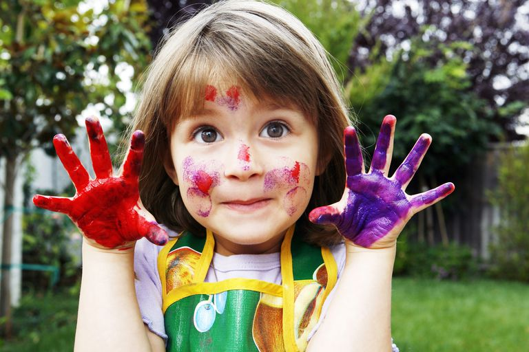 little girl with paint on her hands and face