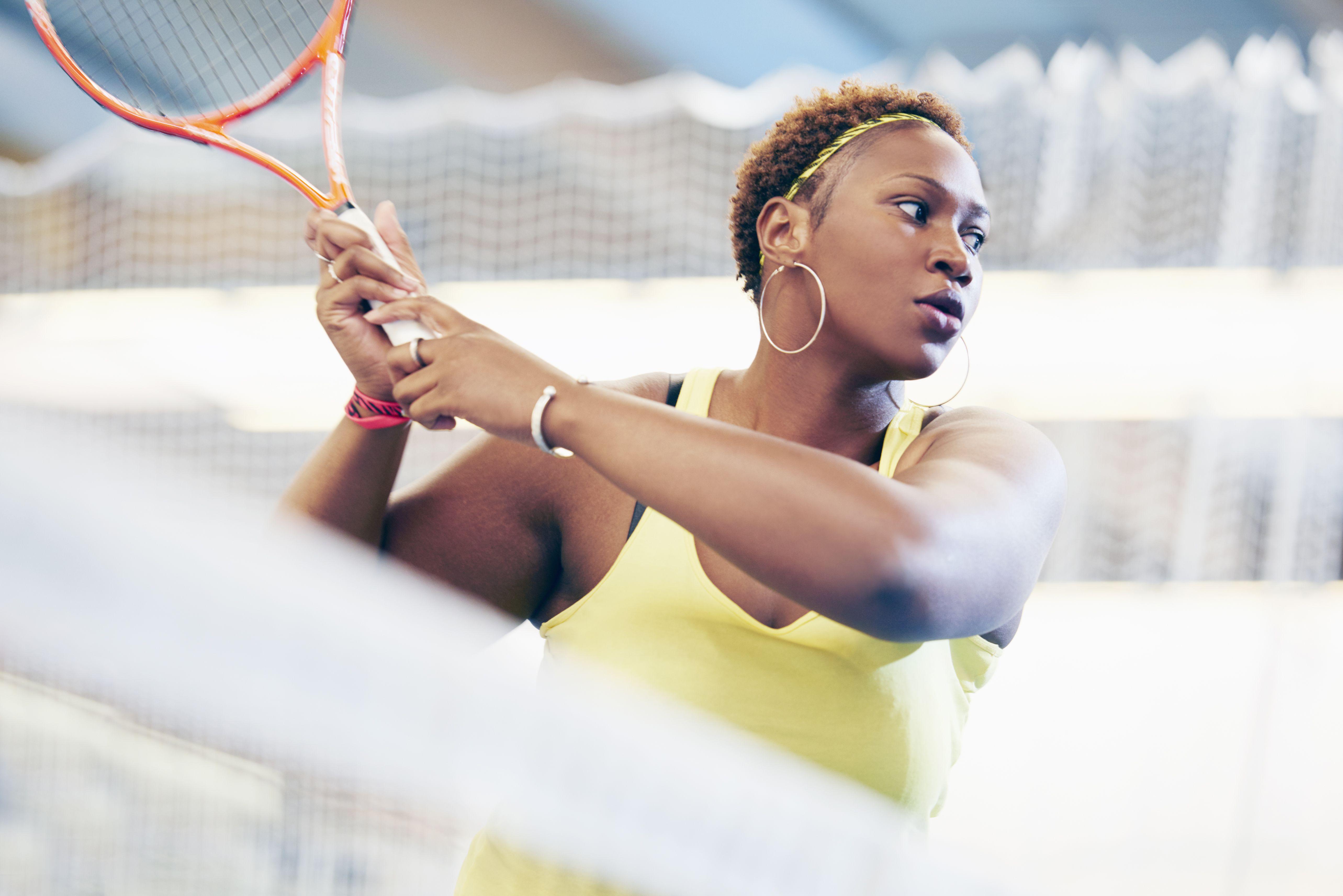 Sports woman on tennis court swinging racket