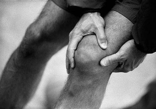 Man's hands grabbing his knee