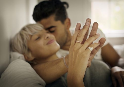 Affectionate young man kissing woman while holding hand in bedroom