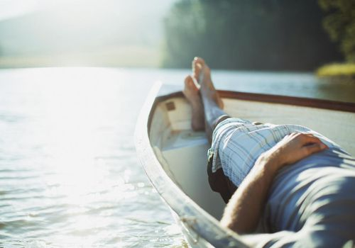 Man's taking a nap in a row boat