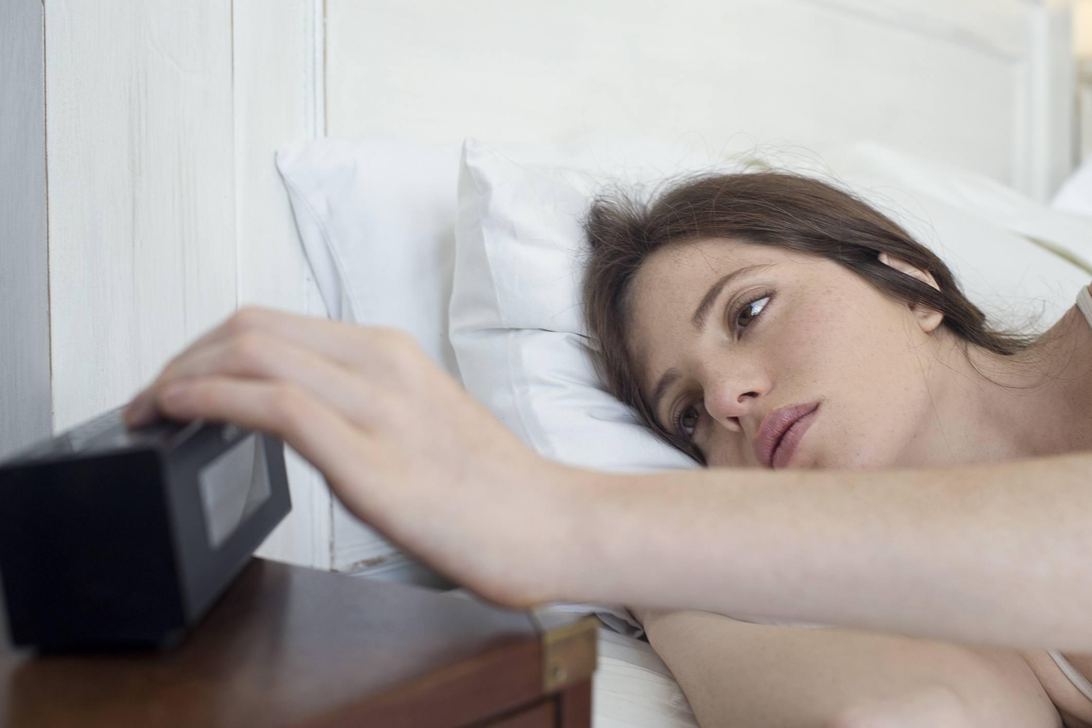 woman hitting snooze on alarm clock