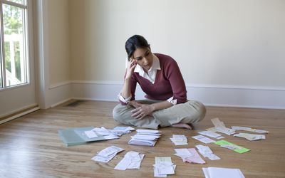 a seated woman looking at bills and receipts on floor
