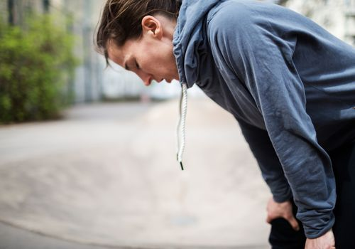 Woman bending over breathing deeply