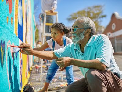 old man and little girl painting a mural
