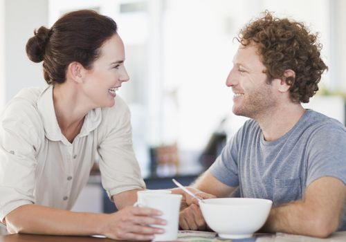 Smiling couple talking at breakfast table