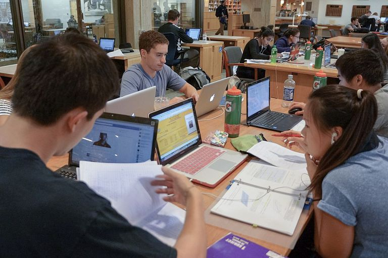 college students sit together studying in library