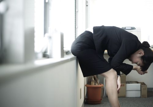 Stressed businesswoman leaning on a windowsill and bending over