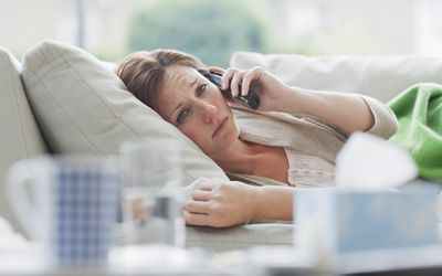 Sad, sick woman laying on the couch talking on the phone