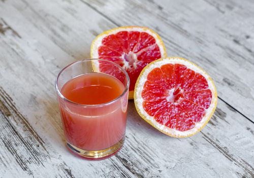 Sliced grapefruit and glass of grapefruit juice on wood