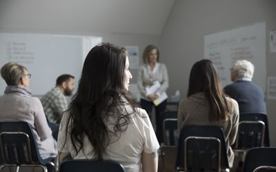Thoughtful woman at support group in community center