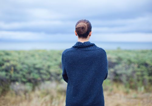 Woman in blue cardigan looking out on cloudy horizon