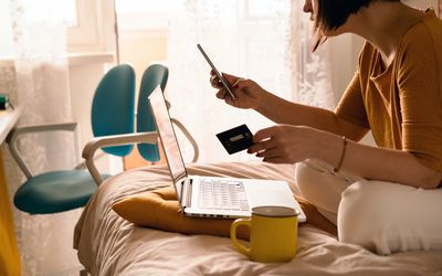 A woman sits on her bed, holding a credit card and a phone, while looking at a computer and shopping online.