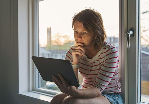 Woman using digital tablet on window sill