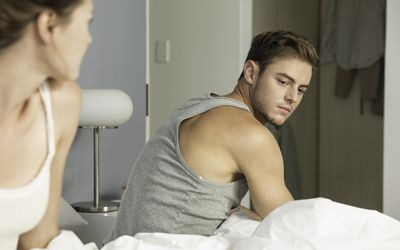 Unhappy young couple getting up from bed
