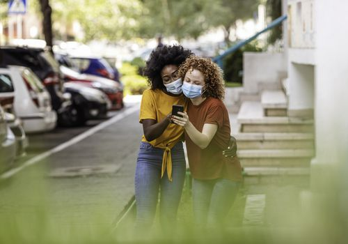 Multi ethnic Friends having fun in city, wearing surgical protective mask against pandemic, using smartphone.