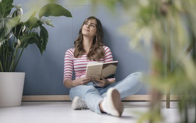 Woman holding a book looking off into the distance