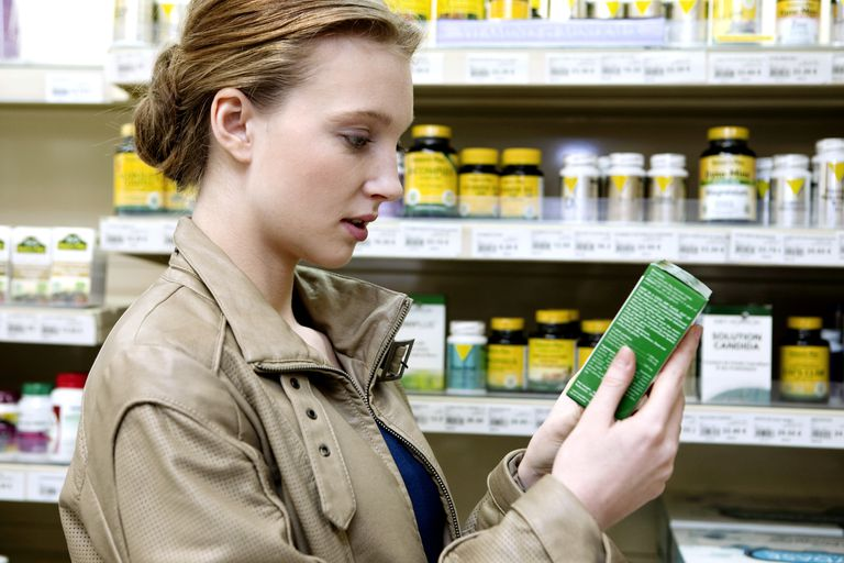woman reading the label on a box of supplements in a store