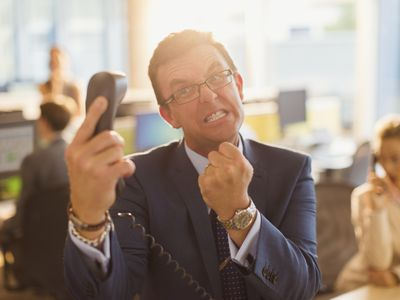 Furious businessman gesturing with fist at telephone in office