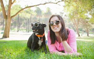 A woman and a dog wearing sunglasses