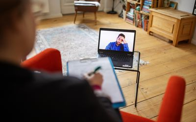 Man having a cognitive behavioral therapy video call with mental health professional
