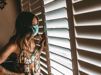 A woman wearing a mask looks out a window from behind blinds in a dark room.