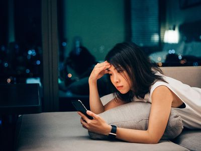 Young Asian businesswoman working late and checking work email on mobile at home