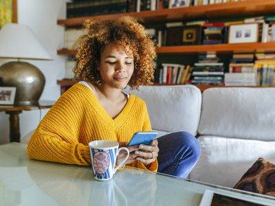 Woman with tea looking at her phone