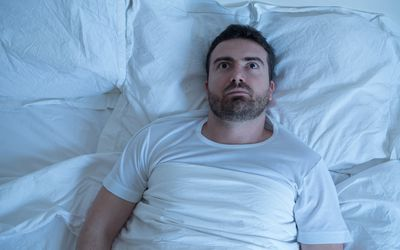 man in bed with eyes open