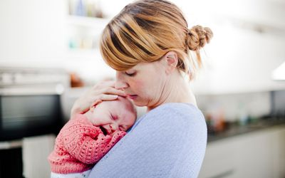 Mother holding crying newborn daughter