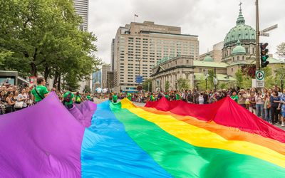 People are holding a giant gay rainbow flag over the street at gay pride parade.