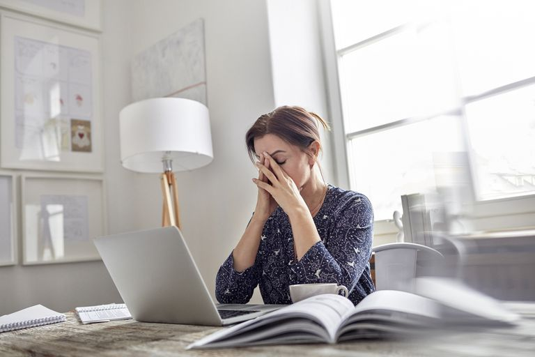 tired woman with her eyes closed at her desk