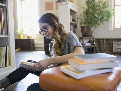 Woman reading books on living room floor