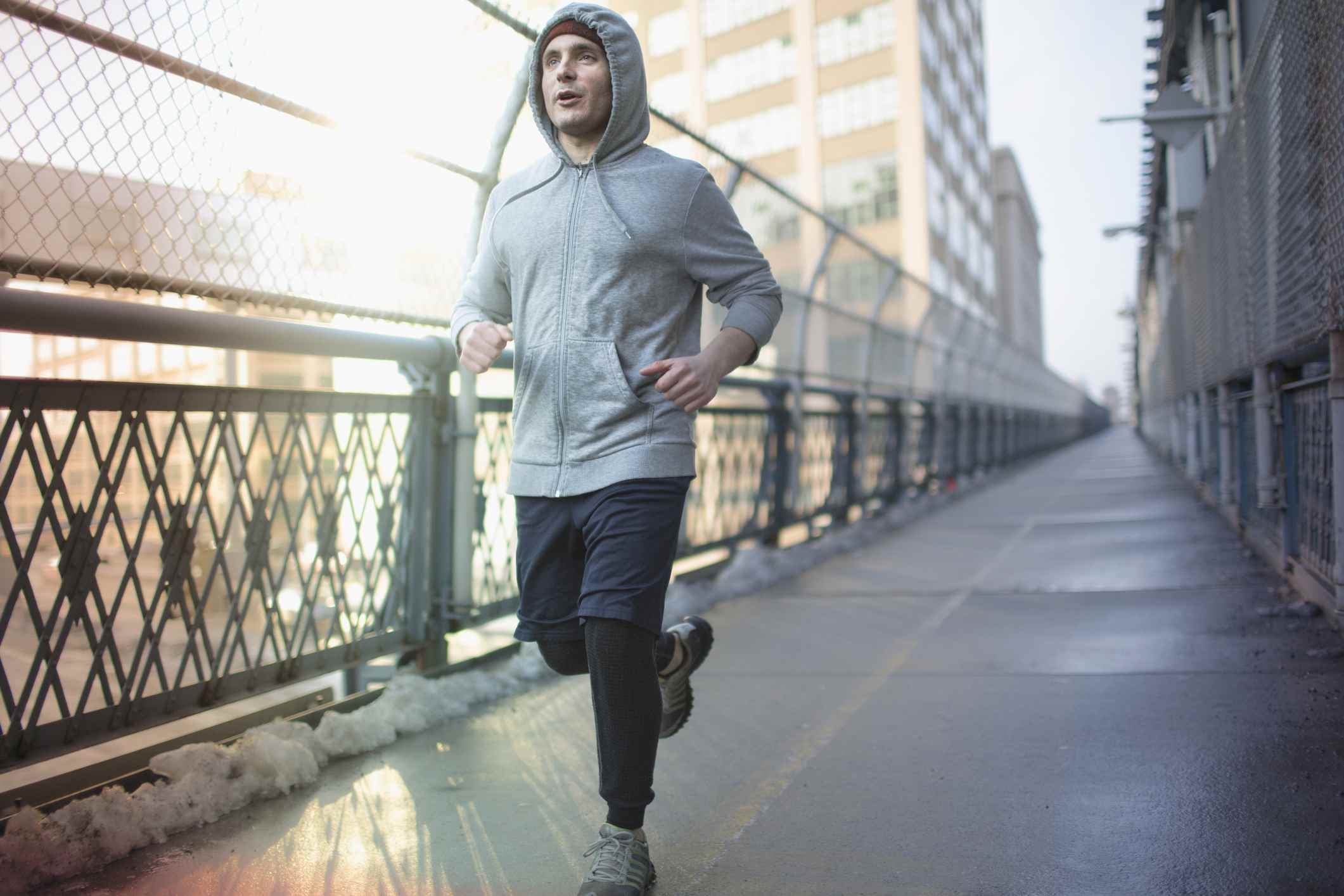 adult man running across bridge