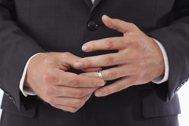 man's hands taking off wedding ring